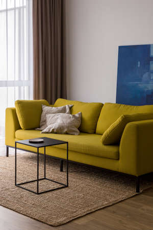 Bright living room with modern yellow sofa, simple, cubic, black coffee table and natural rug