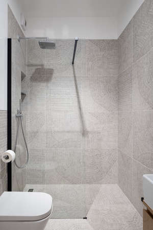 Spacious shower behind glass wall in modern bathroom with decorative, patterned tiles
