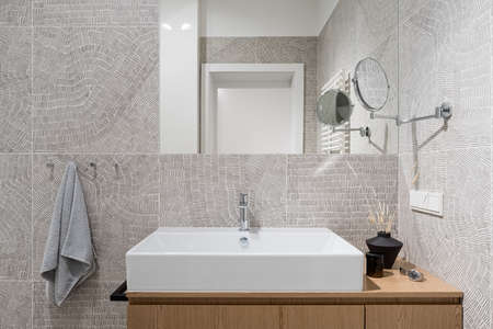 Stylish, white washbasin with wooden cabinet in new bathroom with modern, patterned tiles