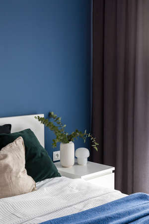 Simple white bedside table with decorations next to cozy bed in bedroom with blue wall