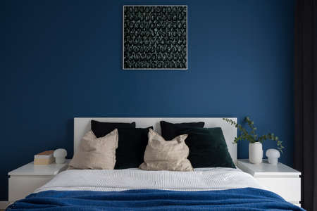Modern navy blue wall in simple bedroom with cozy, double bed and two bedside tables with lamps and decorations Banque d'images