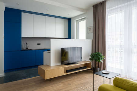 Modern kitchen with white and blue furniture open to small living room with tv on wooden sideboard and big window