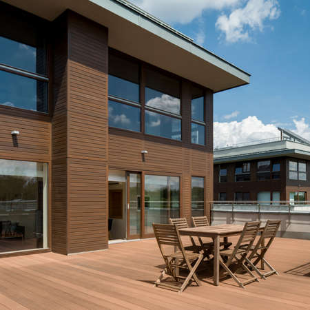 Spacious terrace with wooden floor, chairs and table in modern residential building, exterior view