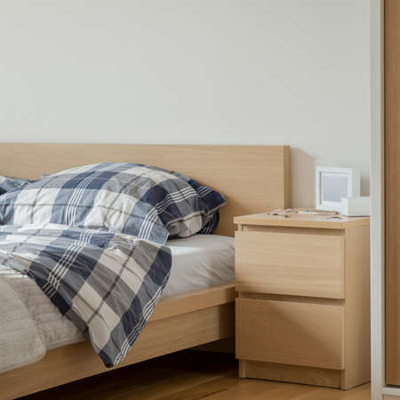 Wooden bedside table with two drawers next to comfortable bed with wooden frame and headboard in simple bedroom Banque d'images