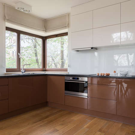 Spacious and modern kitchen with wooden floor, big window and brown and white furniture