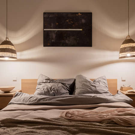 Comfortable, double bed with nice bedclothes, wooden bedside tables and two rattan pendant lamps with warm light in elegant bedroom Banque d'images