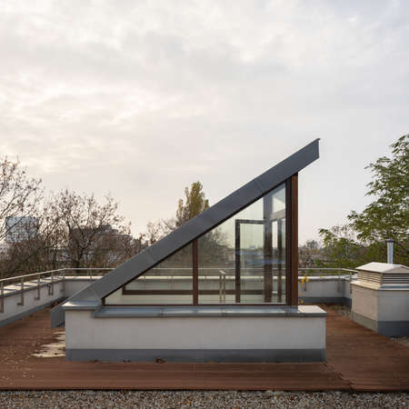 Exterior view of small roof terrace with stylish entry, wooden floor and city view Banque d'images