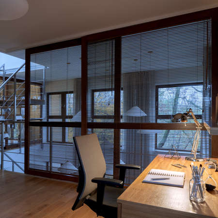 Stylish window wall with blinds in small and cozy home office room with wooden desk