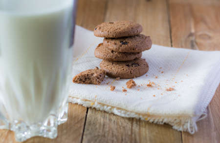 binge: glass of milk and butter cookies chocolate chip on wooden table Stock Photo
