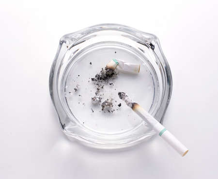 backgroud: Cigarette with glass ashtray on white backgroud Stock Photo