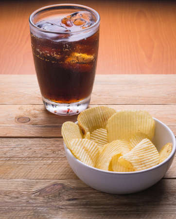 potato: Cola and potato chips on a wooden background Stock Photo