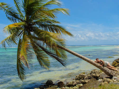 ess: Woman on a coconut tree leaning over the Caribbean sea in Guadeloupe, Antilles.