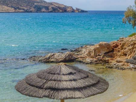 cycladic: Ombrello di paglia sulla spiaggia Parasporos Cicladi Paros in Grecia.