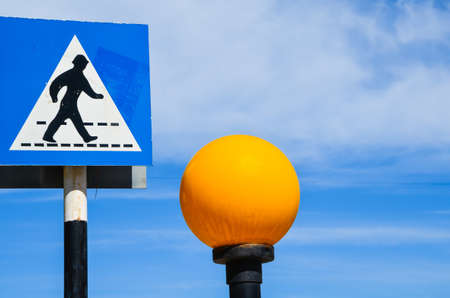 floor lamp: Greek crosswalk sign pedestrian crossing black and blue on a pole and floor lamp with bright orange globe in the blue sky of Cyprus
