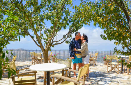 ess: Couple of lovers kissing under trees in a restaurant with panoramic terrace on the Aegean sea and Naxos island in Cyclades, Greece.