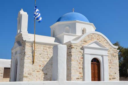 cycladic: Bella chiesa greco di pietra con cupola blu e le pareti imbiancate, con croce e bandiera greca, nell'isola cicladica di Paros in Grecia.