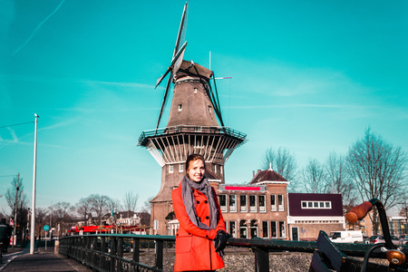dutch girl: Photo of Girl in front of a windmill in Amsterdam, Netherlands
