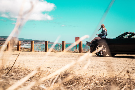 Photo of Girl on top of Convertible at Half Moon Bay, California