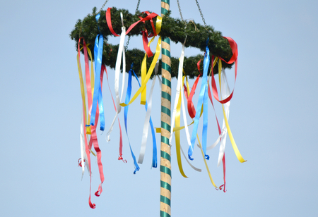 Colorful german maypole in front of blue sky at spring Stock Photo