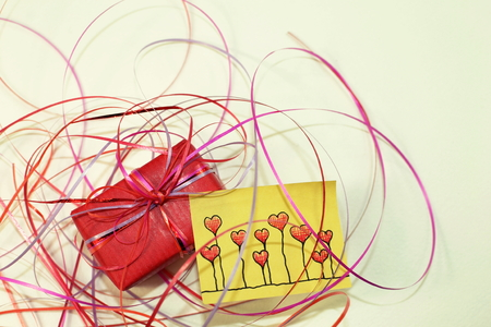 A red gift and a sticky note with hand drawn hearts on a white background.