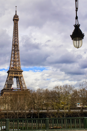 View of the eiffel tower from the bir hakeim bridge with a typical lamp in the foreground