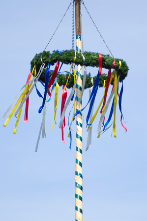 A colorful german maypole in front of blue sky and behind cherry bloom in springtime Stock Photo