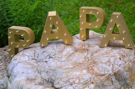 The word PAPA spelt out with large golden block letters. Shot horizontally against a green meadow and a big stone. Reklamní fotografie