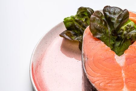 a big fragment of raw atlantic salmon steak with green salad on a pink plate