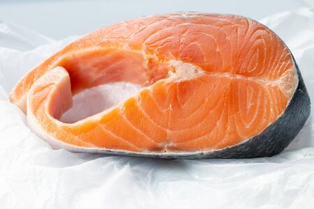 a big piece of raw atlantic salmon steak on a creased piece of paper