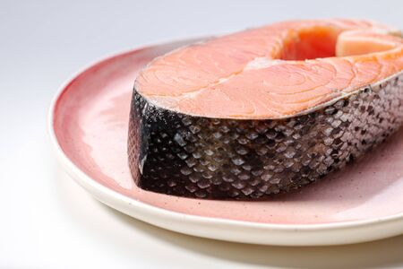 a big piece of uncooked salmon steak on a pink plate