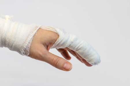 a left injured woman's hand with a bandaged index finger on a white background, side view