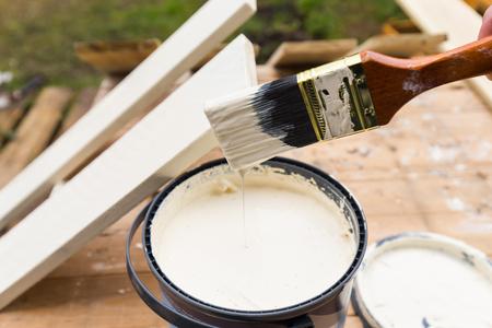 Sosteniendo un cepillo de pintura sobre el frasco con la pintura blanca. Pintura Las planchas de madera exterior con la pintura blanca o emulsión de color blanco utilizando 2 pulgadas pincel de pintura. Foto de archivo