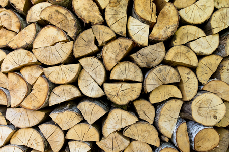 woodshed: Firewood texture background. Chopped birch firewood, stacked in woodshed and snowbound