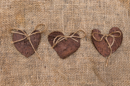 positioned: Three (3) decorative hearts made from tree bark on sackcloth, positioned in the middle of the photo. Hearts decorated with eco twine.