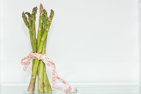 Garden asparagus with measuring tape. Healthy eating. Healthy lifestyle. Diet. Source of vitamins. Vegetarian. Weight loss.