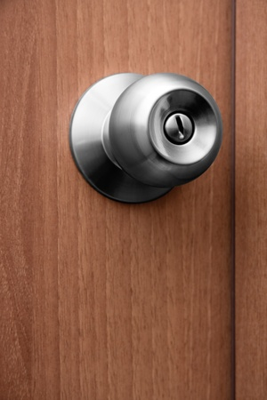 door handle: Close-up shot of a shiny chrome door handle on wooden door. Shallow depth of field. Stock Photo