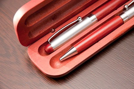 Two ballpoint pens in wooden case on a table backgorund. Stock Photo - 10886151