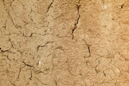 Close up shot of an adobe mud wall with lots of cracks. Stock Photo