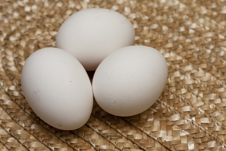 Three white eggs on a straw background. Focus is on eggs.