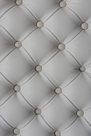 buttoned: White colored leather textured background with buttons.