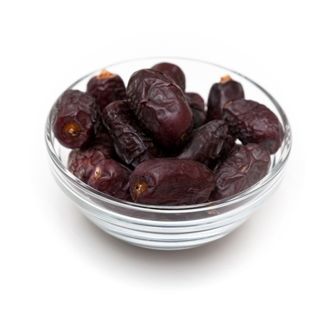 Close up shot of date fruits in a glass bowl isolated on white.
