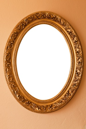 Golden color oval frame on a wall.