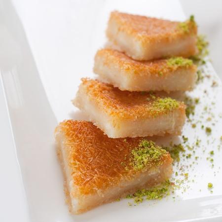 Close up shot of Turkish sweet, kunefe, with pistachios. Stock Photo