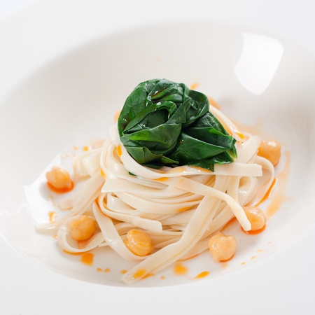 Close up shot of tagliatelle pasta with spinach and chick peas. Stock Photo