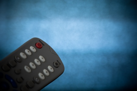Close up shot of a remote control with out of focus tv static.