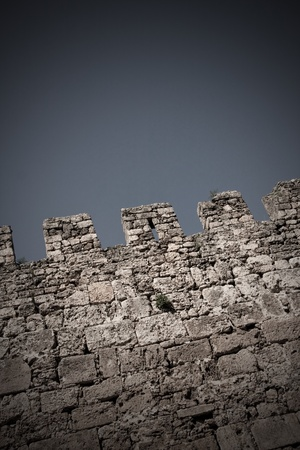 Top of a medieval castle wall against sky. Toned, vignette added.