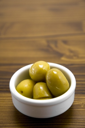 Green olives pot on wooden table. Shallow depth of field.
