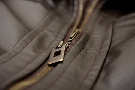 A brown leather jacket close up shot. Focus is on zip.