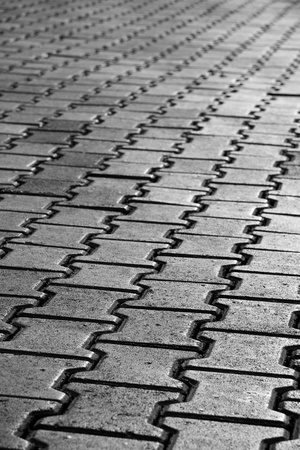 interlocked: Black & White photo of a pavement pattern. Selective focus. Stock Photo