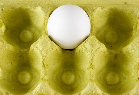Single white egg in yellow egg carton.